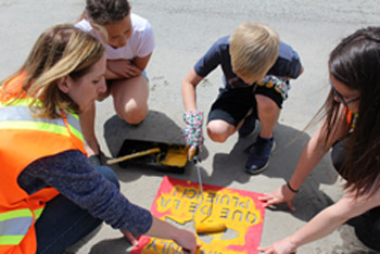 Group painting yellow fish in front of a storm drain